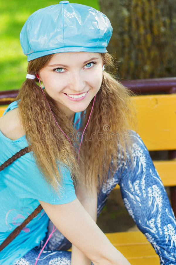 Piękna uśmiechnięta dziewczyna siedzi w parku na ławce i słuchaniu muzyka w błękitnym kapeluszu z różowymi hełmofonami obrazy stock