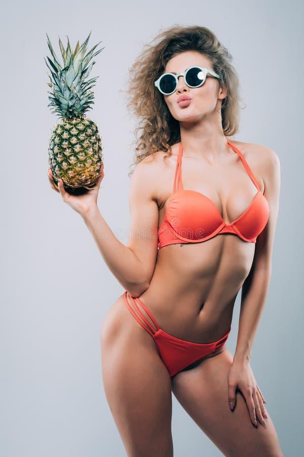 Piękna uśmiechnięta dziewczyna trzyma świeżego ananasa w okularach przeciwsłonecznych, odizolowywającego na bielu obraz royalty free