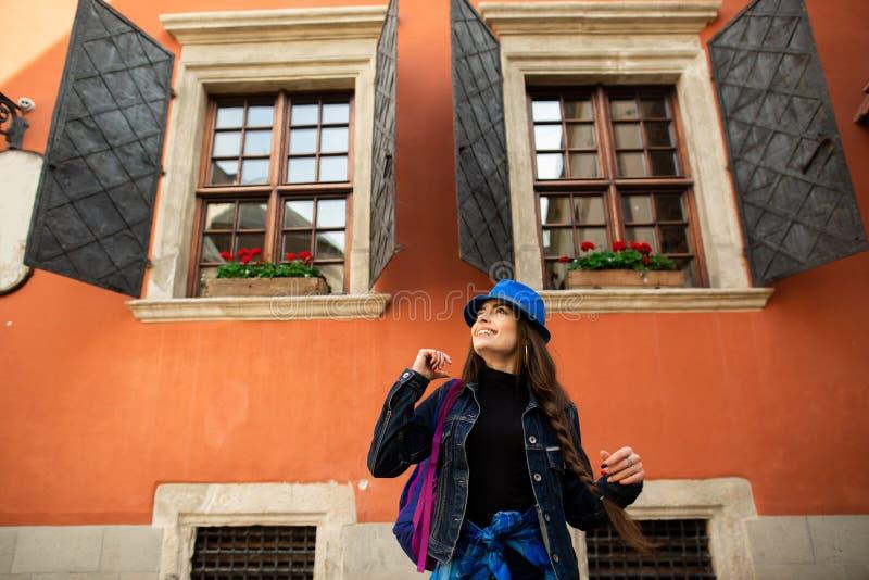 Piękna uśmiechnięta dziewczyna w kapeluszu błękitnych pozach blisko starego czerwień domu obrazy royalty free