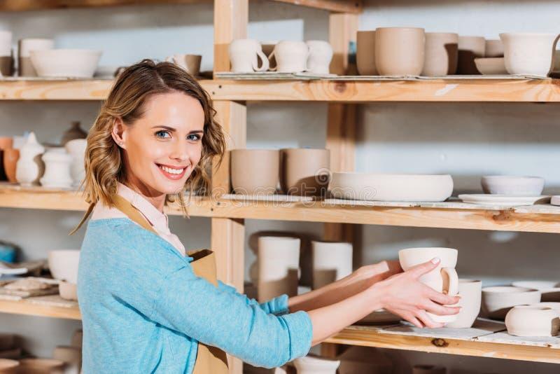 piękna uśmiechnięta garncarka z ceramicznym dishware na półkach obrazy stock