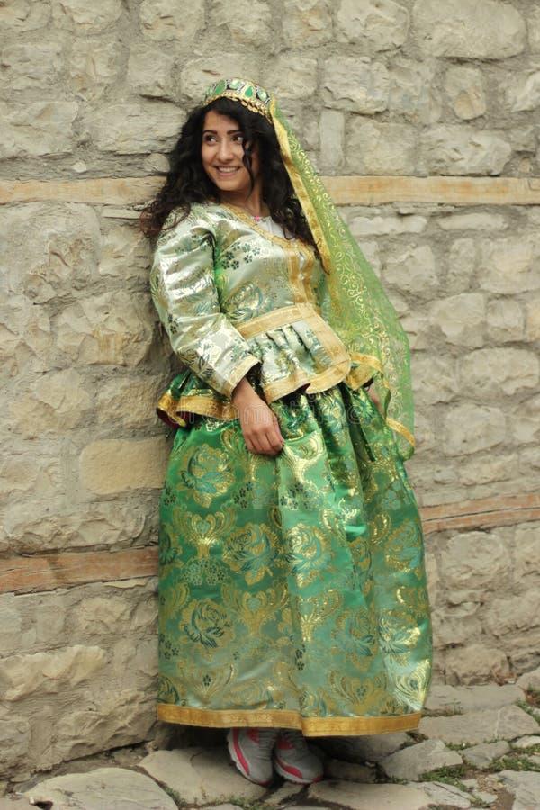 Piękna uśmiechnięta kędzierzawa dziewczyna w Azerbejdżańskim krajowym kostiumu zdjęcia stock