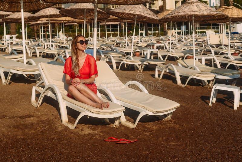 Piękna uśmiechnięta Kaukaska kobieta kłama na bielu w czerwonej przejrzystej tunice i okularach przeciwsłonecznych sunbed na plaż obraz stock