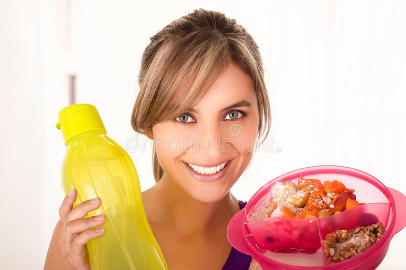 Piękna uśmiechnięta kobieta jest ubranym purpurową koszulkę i trzyma zdrowej owocowej sałatki w jeden ręce i żółtej butelce obrazy royalty free