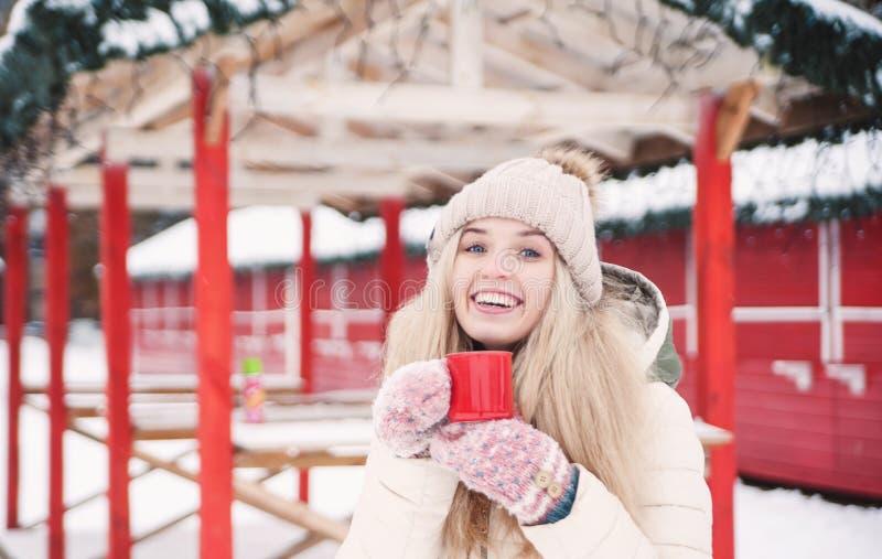 Piękna uśmiechnięta kobieta trzyma filiżankę gorący kakao obraz royalty free