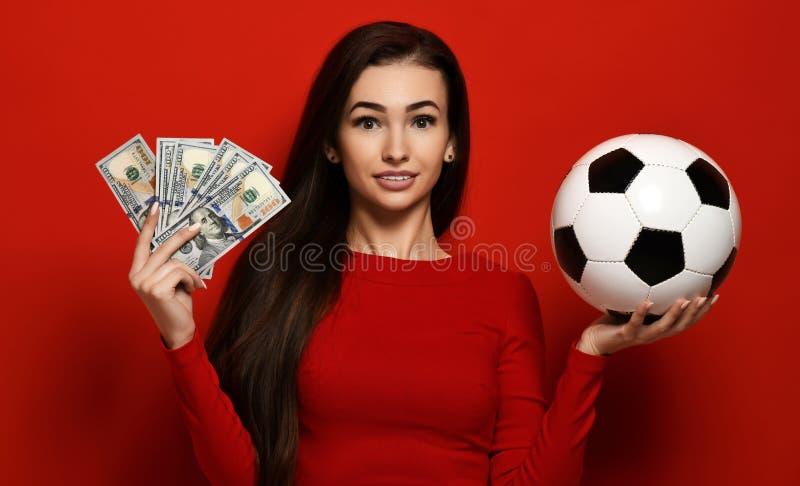 Piękna uśmiechnięta kobieta w ciasnej czerwieni sukni trzyma piłki nożnej piłkę i zwitki dolary zdjęcia stock