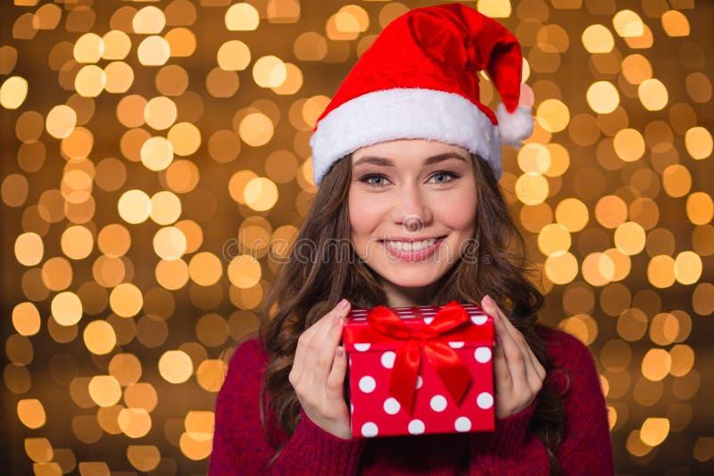 Piękna uśmiechnięta kobieta w Santa Claus kapeluszu z małym prezentem obraz stock
