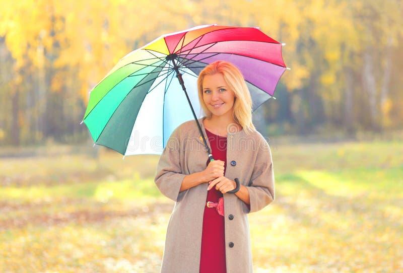 Piękna uśmiechnięta kobieta z kolorowym parasolem w pogodnym jesień dniu obrazy stock
