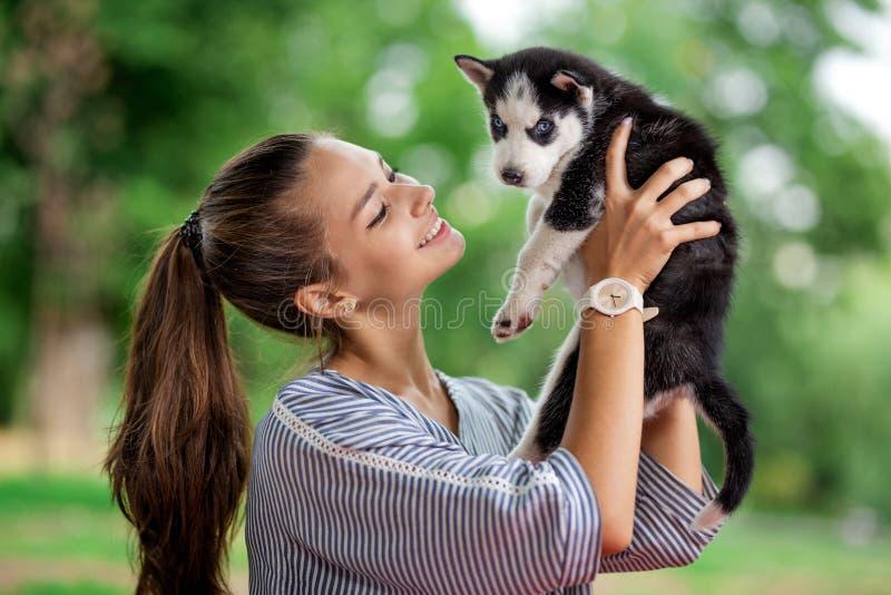 Piękna uśmiechnięta kobieta z ponytail i być ubranym pasiastą koszula cuddling z słodkim łuskowatym szczeniakiem podczas gdy zdjęcie royalty free