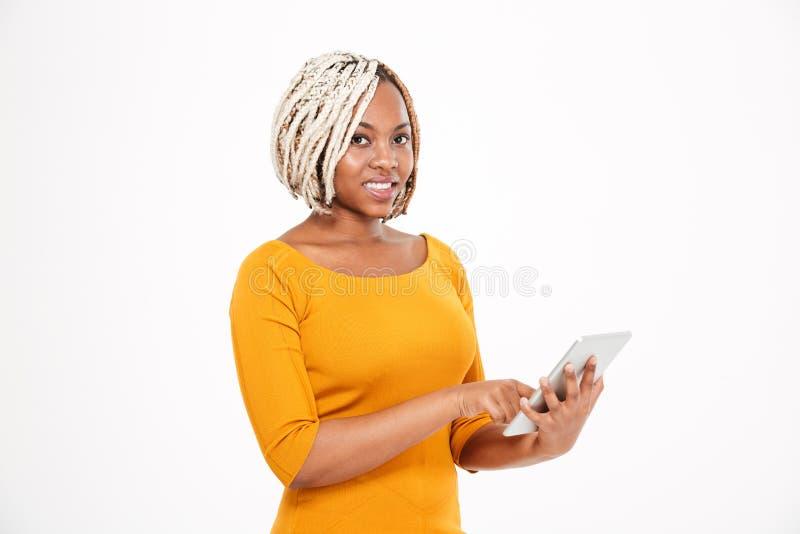 Piękna uśmiechnięta młoda amerykanin afrykańskiego pochodzenia kobieta używa pastylkę fotografia royalty free