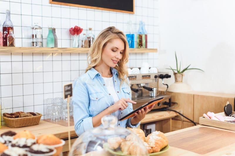 piękna uśmiechnięta młoda kelnerka używa cyfrową pastylkę obrazy stock