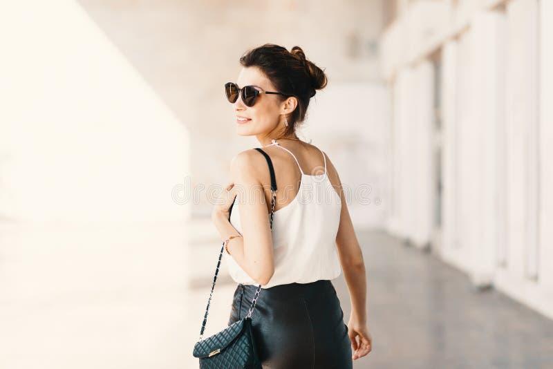 Piękna uśmiechnięta młoda kobieta patrzeje daleko od nad th w okularach przeciwsłonecznych fotografia stock