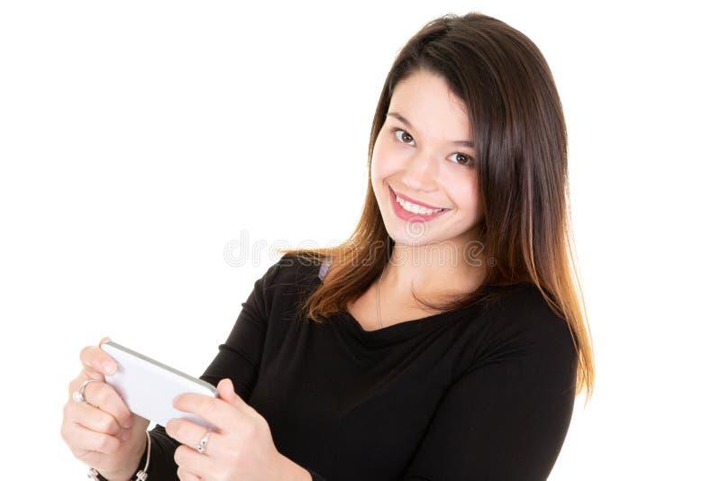 Piękna uśmiechnięta młoda kobieta trzyma smartphone podczas gdy wysylanie sms texting odizolowywam na białym tle fotografia royalty free