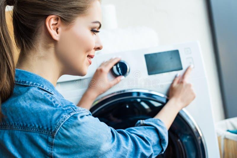 piękna uśmiechnięta młoda kobieta używa pralkę zdjęcie royalty free