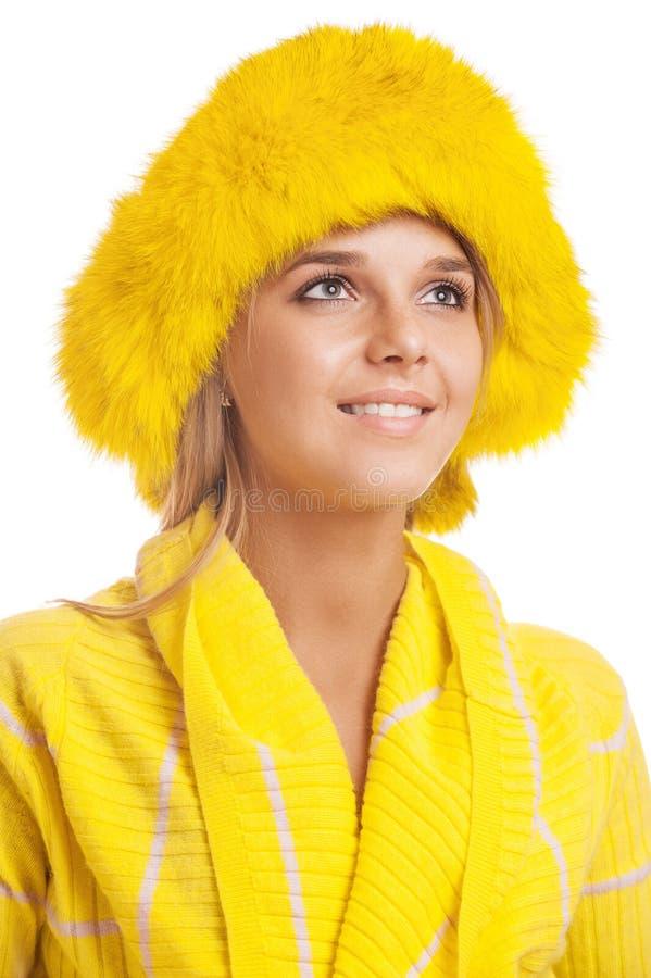 Piękna uśmiechnięta młoda kobieta w żółtym futerkowym kapeluszu zdjęcia stock