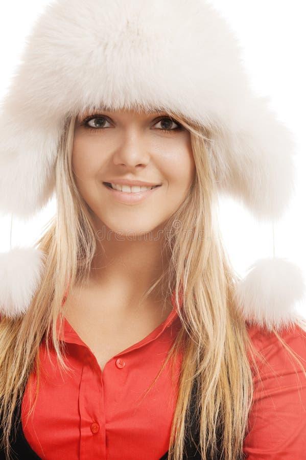 Piękna uśmiechnięta młoda kobieta w białym futerkowym kapeluszu czerwieni koszula i obraz stock