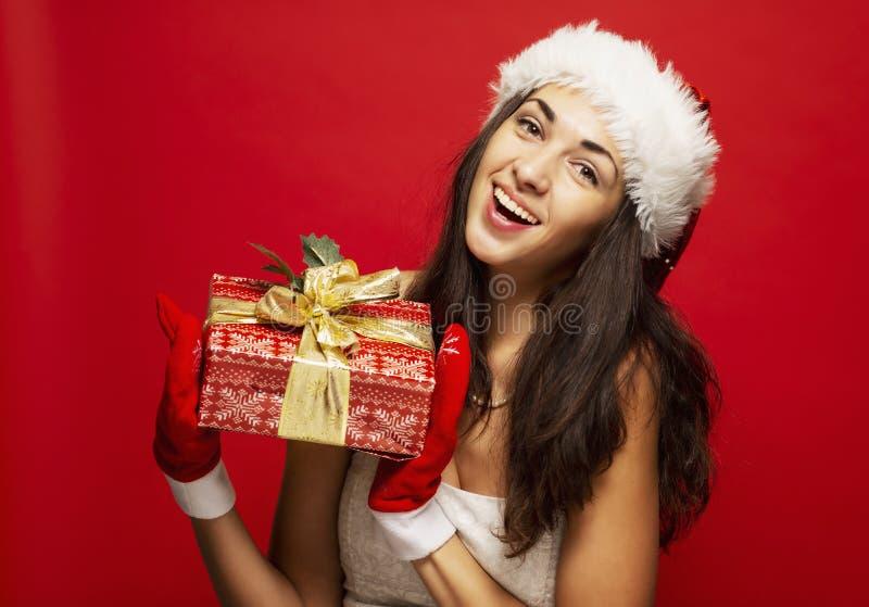Piękna uśmiechnięta młoda kobieta w Bożenarodzeniowym kapeluszu z prezentem w ręce, w górę zdjęcia royalty free