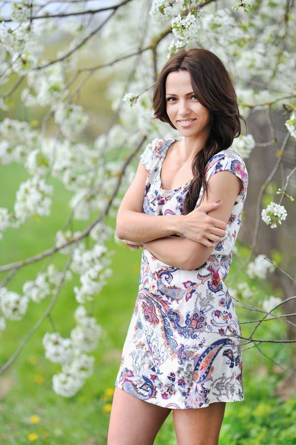 Piękna uśmiechnięta młoda kobieta w parkowej pozyci z rękami składa obrazy royalty free