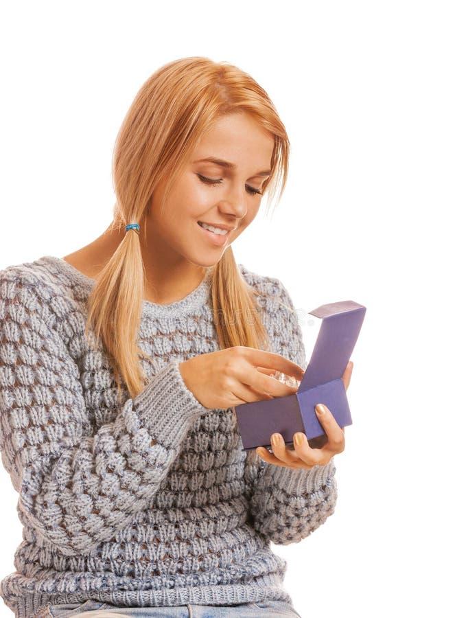 Piękna uśmiechnięta młoda kobieta w szarego puloweru przyglądającym prezencie w bo obrazy stock