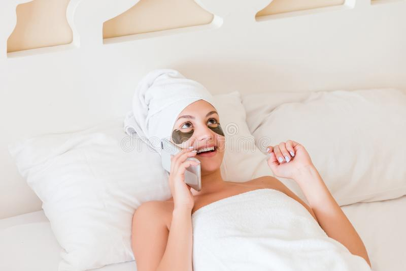 Piękna uśmiechnięta młoda kobieta z poniższymi oko łatami i opowiadać telefon komórkowy w bathrobe lying on the beach w łóżku Szc obraz royalty free