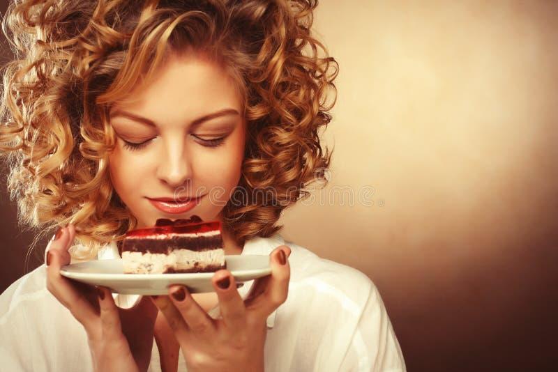 Piękna uśmiechnięta młoda kobieta z tortem obrazy stock