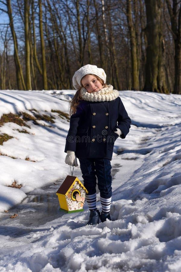 Piękna uśmiechnięta mała dziewczynka trzyma ptasiego dom w parku obraz stock