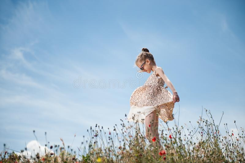 Piękna uśmiechnięta mała dziewczynka w okulary przeciwsłoneczni sztukach z jej suknią dmuchającą wiatrem obrazy stock