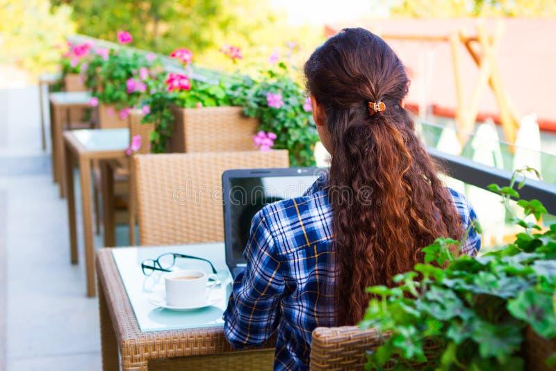 Piękna uśmiechnięta modniś kobieta używa laptop przy uliczną kawiarnią, biznesowy pojęcie obraz royalty free