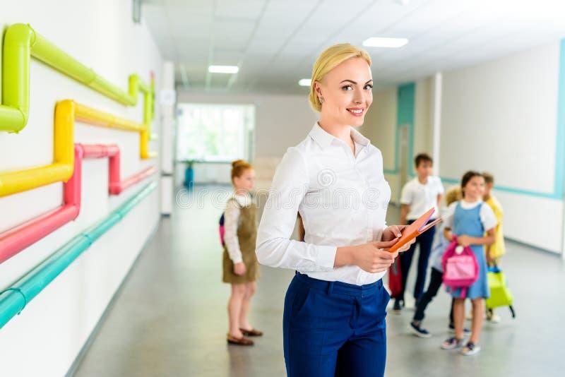 piękna uśmiechnięta nauczyciel pozycja przy szkolnym korytarzem z dziećmi zdjęcia stock