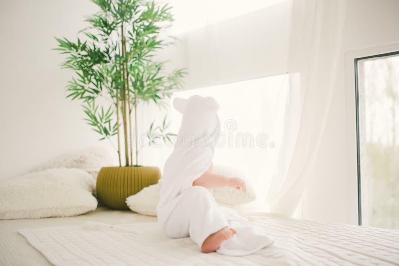 Piękna uśmiechnięta nowonarodzona chłopiec zakrywająca z białym bambusowym ręcznikiem z zabawa ucho Siedzący na białej dzianinie, zdjęcie royalty free