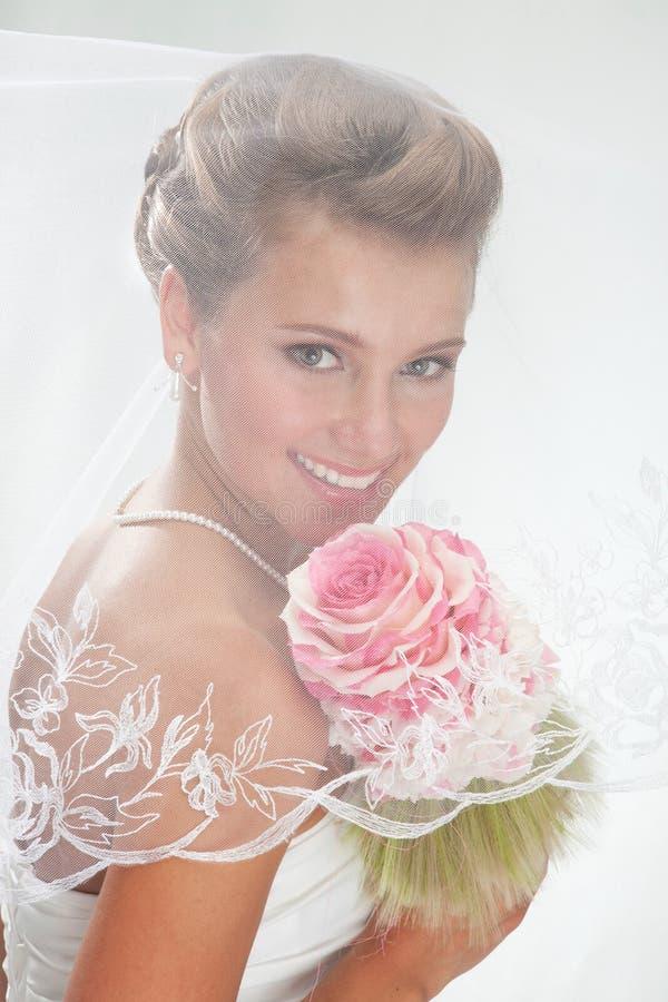 Piękna uśmiechnięta panna młoda w przesłonie z bukietem zdjęcie stock
