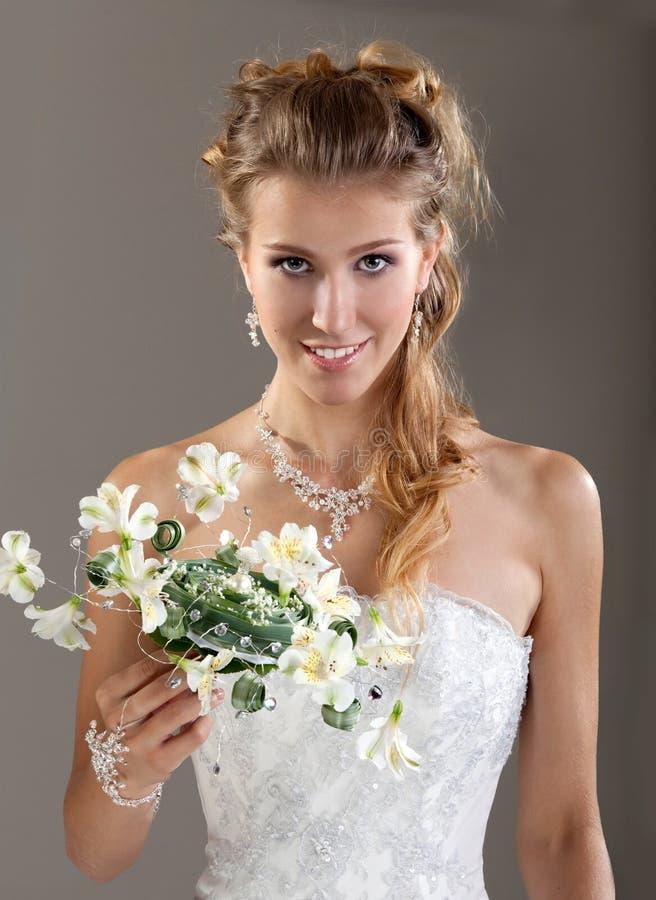 Piękna uśmiechnięta panna młoda w przesłonie z bukietem Szary Backgroun fotografia stock
