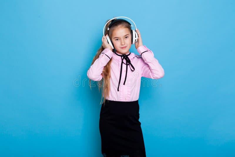Piękna uczennica słucha muzyki w dużych słuchawkach fotografia stock