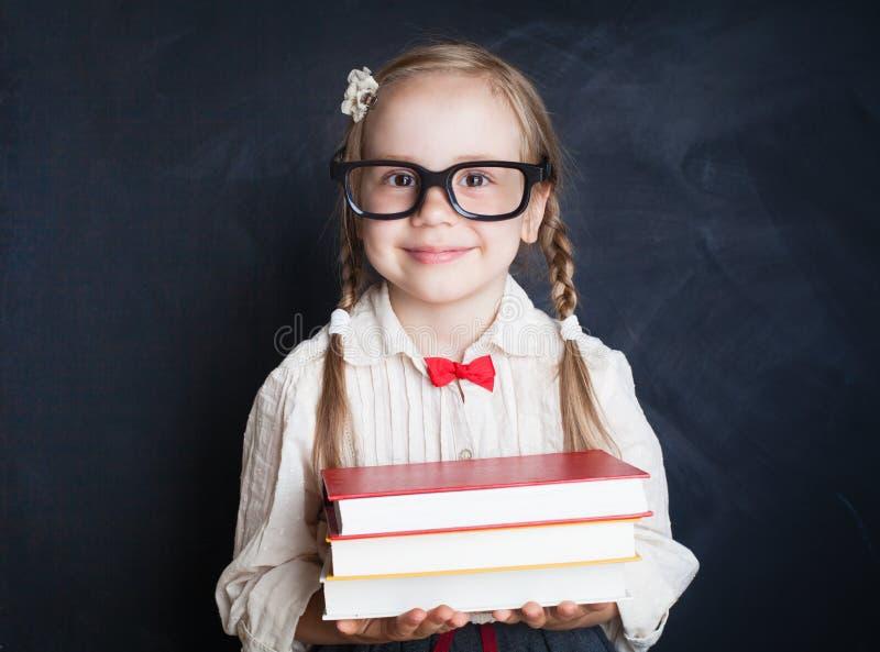 Piękna uczennica z książką na kredowej deski tle zdjęcia royalty free