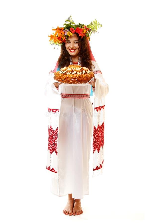 Piękna ukraińska młoda gościnna kobieta w rodzimym kostiumu obok zdjęcia stock