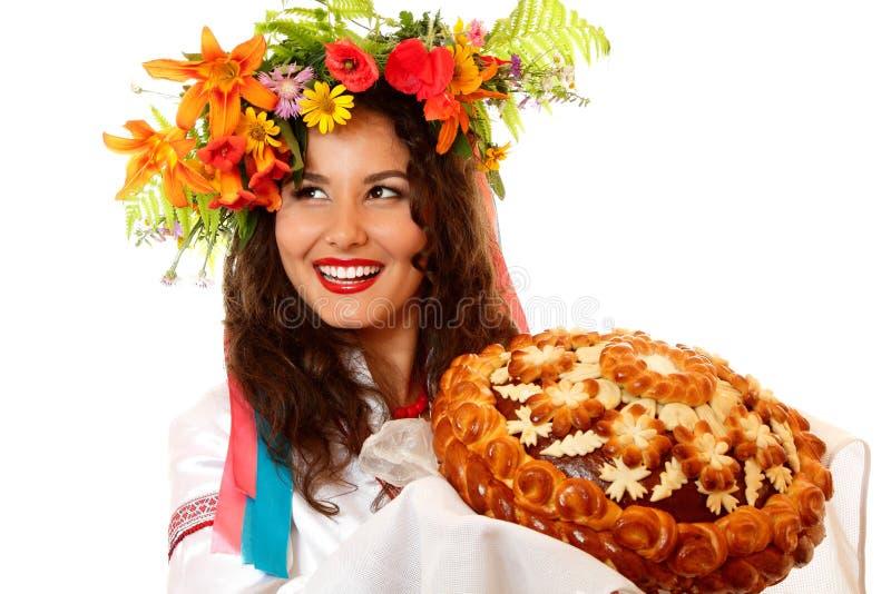 Piękna ukraińska młoda gościnna kobieta w rodzimym kostiumu obok obraz stock