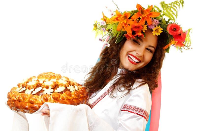 Piękna ukraińska młoda gościnna kobieta w rodzimym kostiumu obok obrazy stock