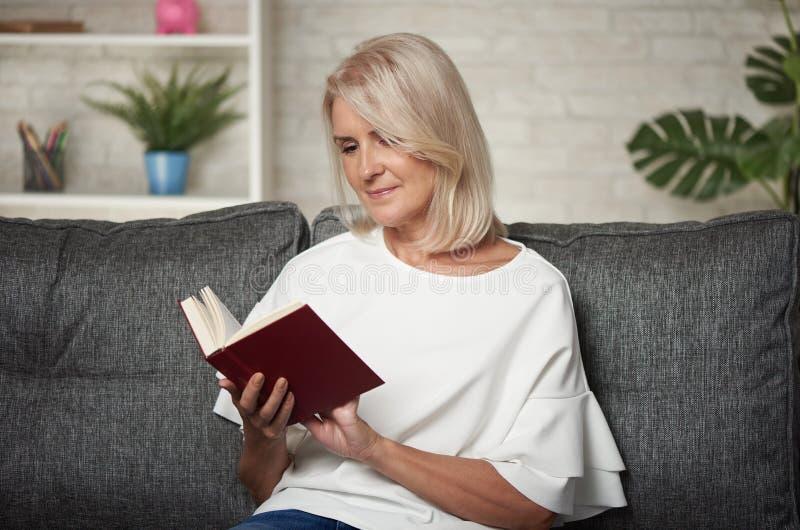 Piękna w średnim wieku blondynki kobieta czyta książkę w domu zdjęcia royalty free
