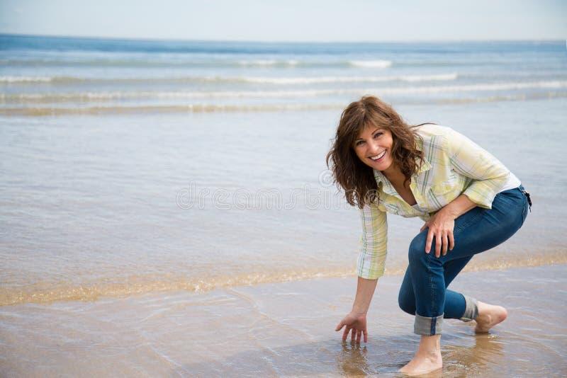 Piękna w średnim wieku kobieta ma zabawę na plaży obrazy royalty free