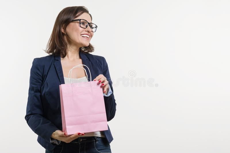 Piękna w średnim wieku kobieta otwiera torba na zakupy, biały tło, zdjęcie stock