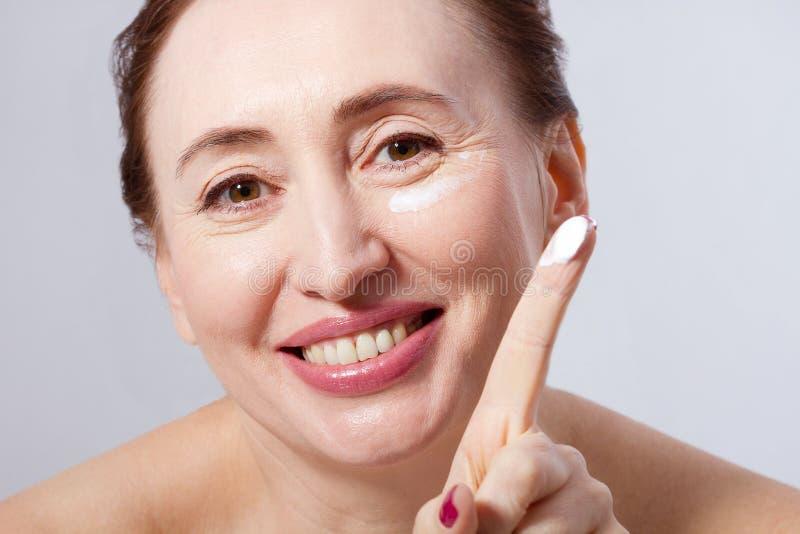 Piękna w średnim wieku kobieta stosuje kosmetycznego kremowego traktowanie na twarzy odizolowywającej na popielatym tle Egzamin p zdjęcie stock
