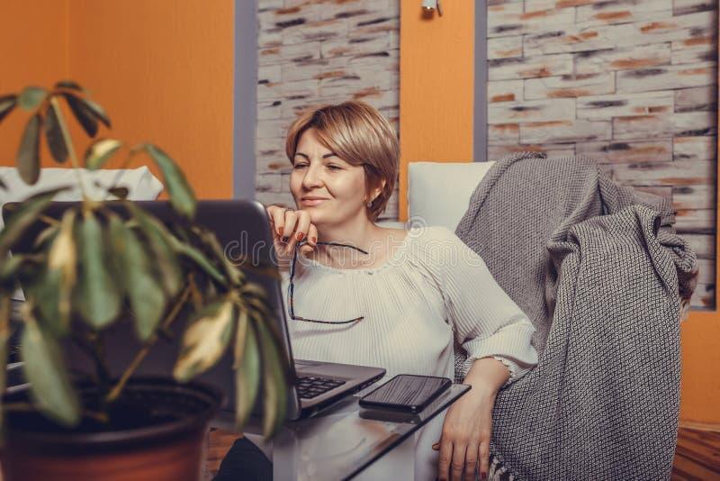 Piękna w średnim wieku kobieta używa jej laptop w wygodzie jej żywy pokój obraz stock