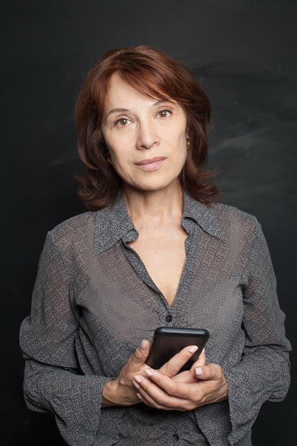Piękna w połowie dorosła biznesowa kobieta z smartphone zdjęcie stock