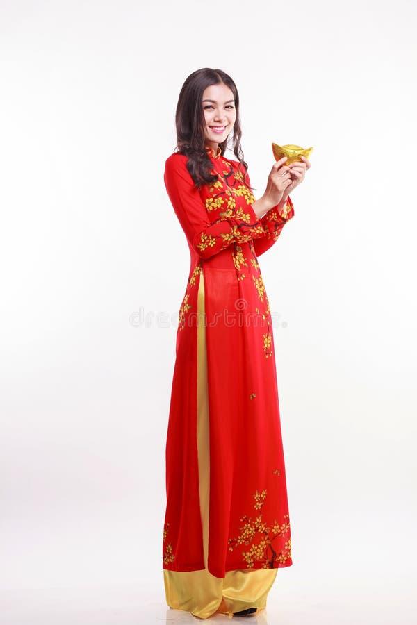 Piękna Wietnamska kobieta z czerwienią ao Dai trzyma szczęsliwego nowego roku ornament zdjęcie stock