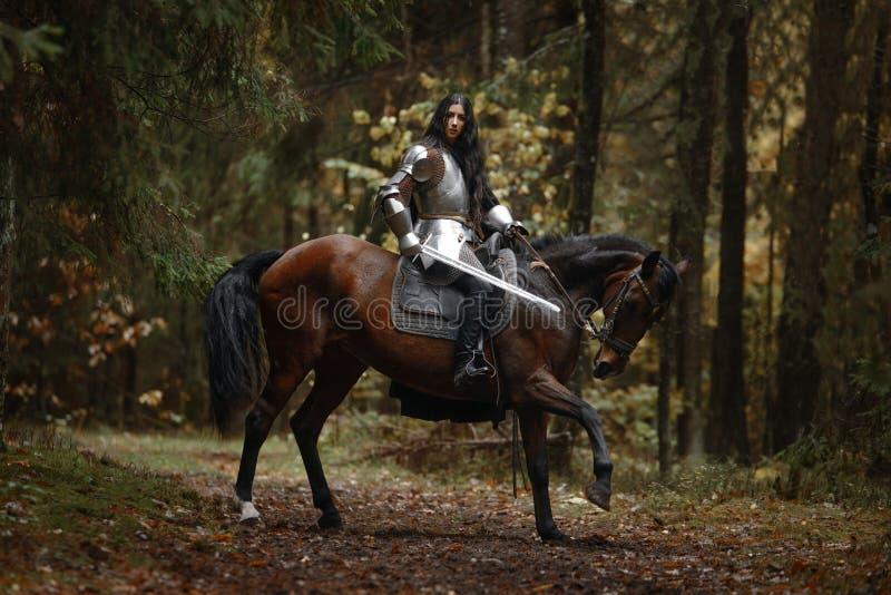 Piękna wojownik dziewczyna jest ubranym chainmail jedzie konia w tajemniczym lesie z kordzikiem i opancerzenie obrazy stock