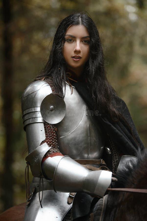 Piękna wojownik dziewczyna jest ubranym chainmail jedzie konia w tajemniczym lesie z kordzikiem i opancerzenie obraz royalty free
