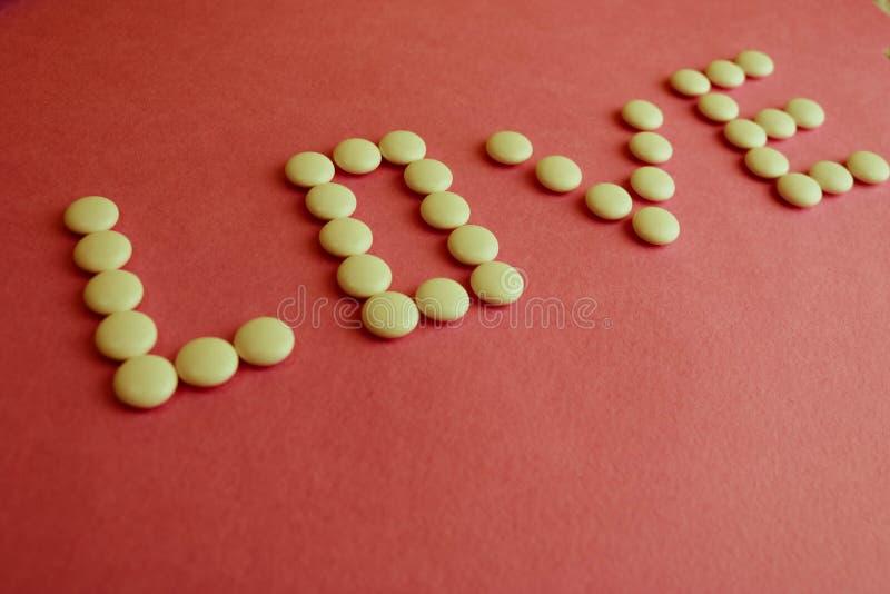 Piękna wpisowa miłość robić od białego round gładkich medycznych pigułek, witamin, antybiotyków i kopii przestrzeni, na jaskrawej zdjęcie royalty free