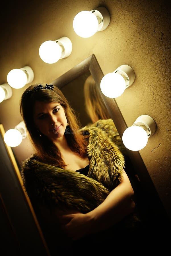 Piękna wspaniała kobieta w futerkowym żakiecie pozuje blisko lustra z żarówką obrazy royalty free