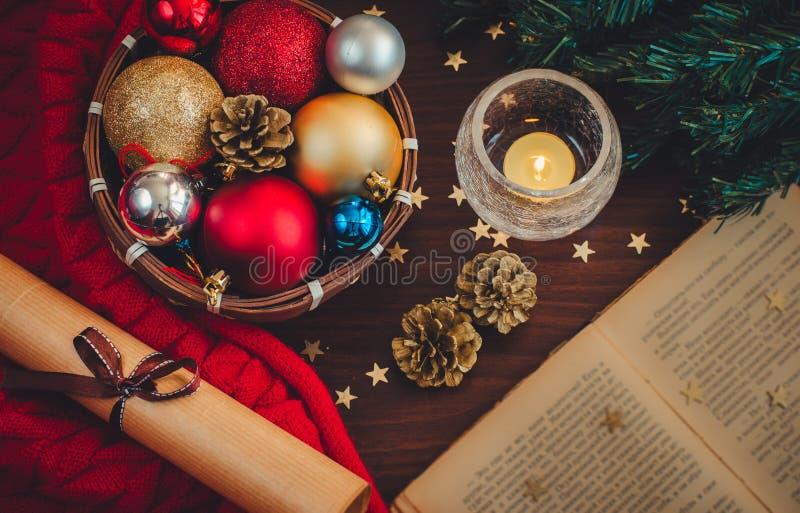 Piękna wygodna boże narodzenie scena z xmas gałąź, mały kosz z kolorowymi piłkami, płonąca świeczka, otwierająca książka, staczaj obrazy stock