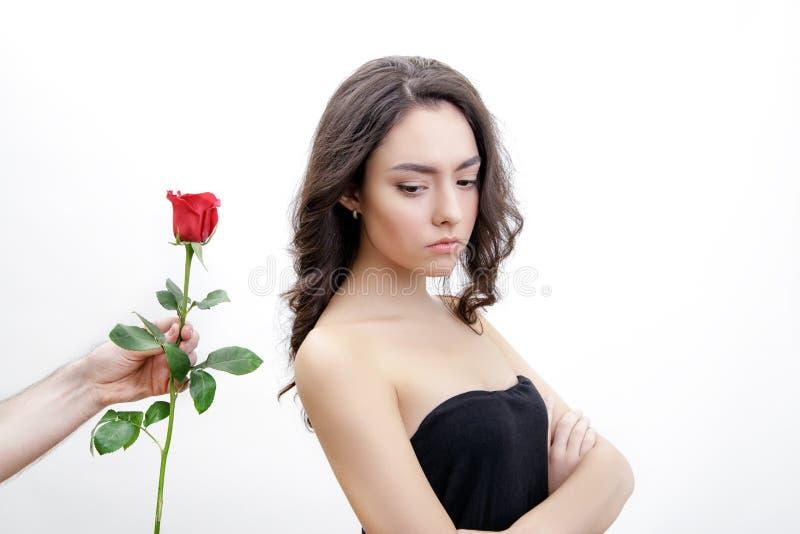 Piękna wzburzona dziewczyna otrzymywa jeden czerwieni róży Patrzeje kwiaty Jest przyglądająca nad jej ramieniem obrazy stock