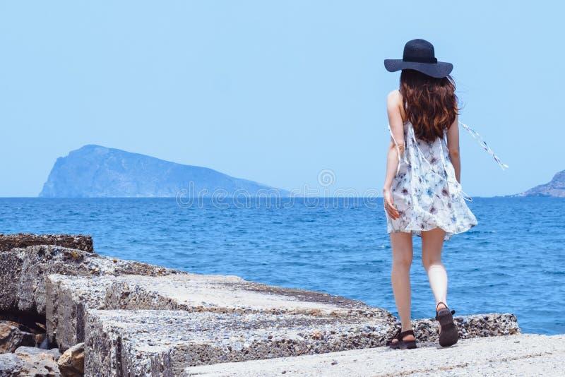 Piękna, zadziwiająca marzycielska dziewczyna, spacery wzdłuż kamiennego mola, cieszy się chluśnięcia wiatr, brązowa skóra, ciemny zdjęcia royalty free